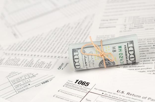 Formulário de 1065 us return of parentship income com rolo de notas de dólar americano