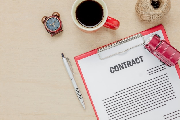 Formulário de contrato comercial com vista superior e caneta de café com fundo de madeira.