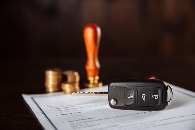 Formulário de contrato para empréstimo de carro, carimbo, caneta e chave do carro na mesa de madeira.