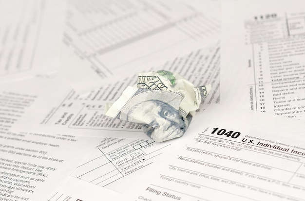 Formulário de declaração de imposto de renda individual e nota de cem dólares amassada