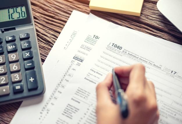 Formulário de imposto 1040 da escrita da mão da mulher que usa o conceito individual do pagamento da declaração de rendimentos da renda da calculadora.