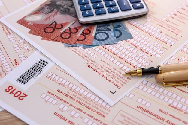 Formulário de imposto australiano com caneta, calculadora e dólares australianos