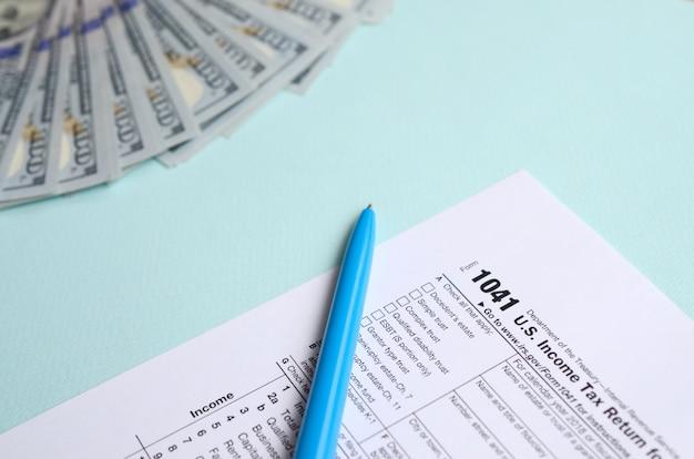 Formulário de imposto fica perto de notas de cem dólares e caneta azul