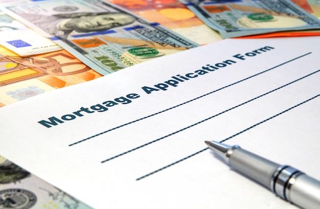 Formulário de pedido de hipoteca com caneta e dinheiro