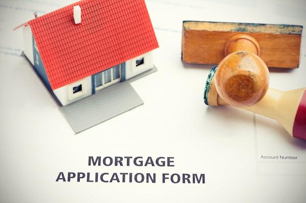 Formulário de pedido de hipoteca com carimbo e casa modelo