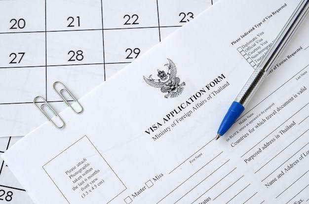 Formulário de pedido de visto de tailândia e caneta azul na página de calendário de papel