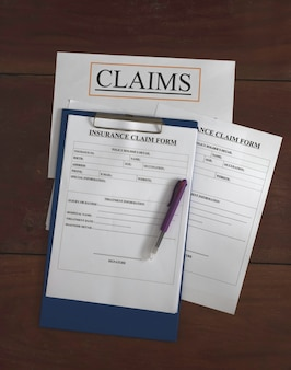 Formulário de reivindicação de seguro colocado na placa de madeira, luz borrada ao redor