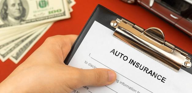 Formulário de seguro automóvel e véchile na mão do agente homem. plano de fundo de dinheiro e brinquedo do carro. foto do banner