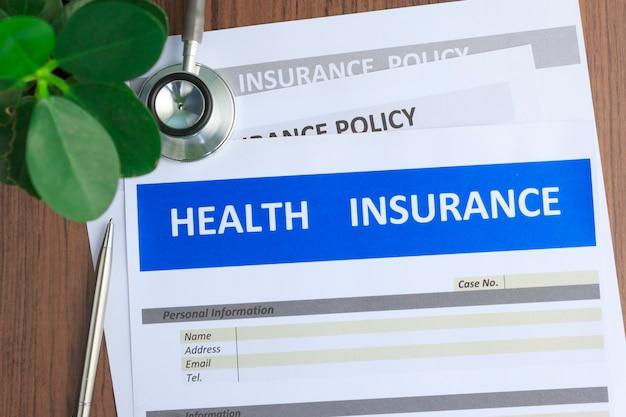 Formulário de seguro de saúde com estetoscópio em vista superior