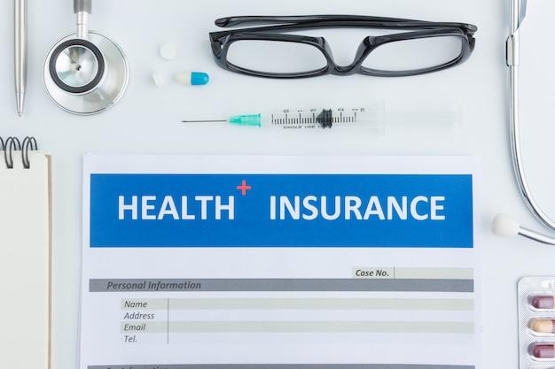Formulário de seguro de saúde com estetoscópio na vista superior
