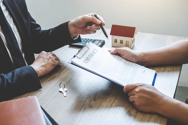 Formulário do contrato do alcance do corretor imobiliário ao cliente que assina a propriedade do contrato do acordo com aprovado