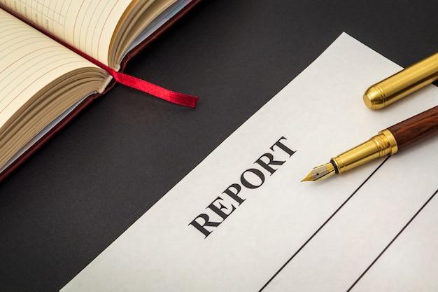 Formulário em branco e caneta para elaboração de relatório na tabela preta