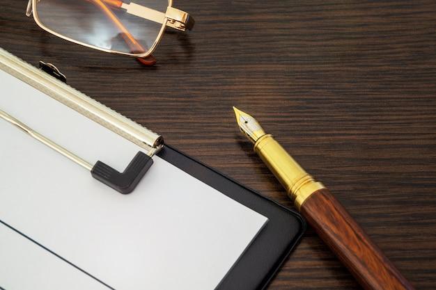 Formulário em branco vazio e caneta para elaboração de relatório na mesa de madeira marrom