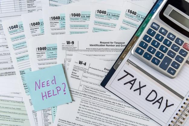 Formulário fiscal 1040 com bloco de notas e hora do imposto de texto, caneta e calculadora. conceito de imposto