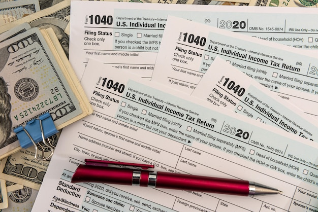 Formulário fiscal 1040 conosco notas de 100 dólares, conceito de contador econômico
