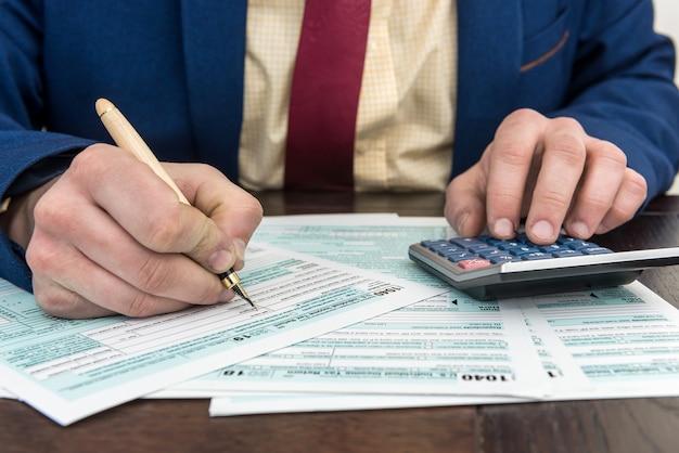 Formulário fiscal 1040 de documento financeiro contábil e preenchimento de homem com calculador. tempo para imposto