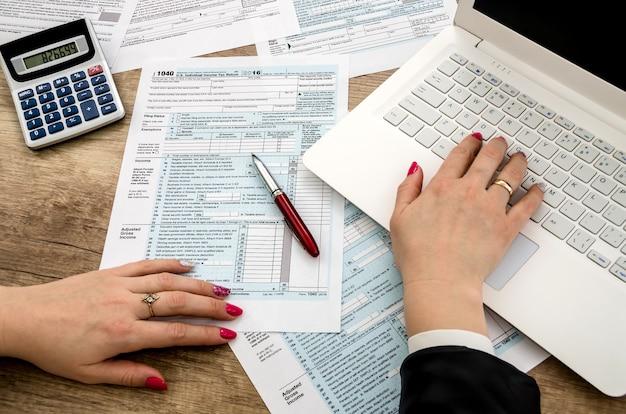 Formulário fiscal 1040 mãos humanas e laptop
