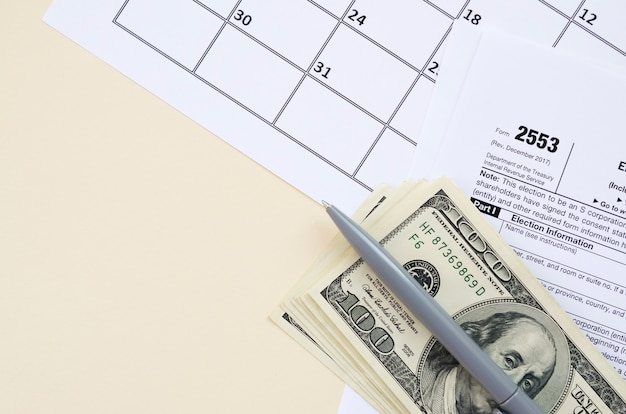 Formulário irs 2553 a eleição por um imposto em branco da small business corporation encontra-se com caneta e muitas notas de cem dólares na página do calendário