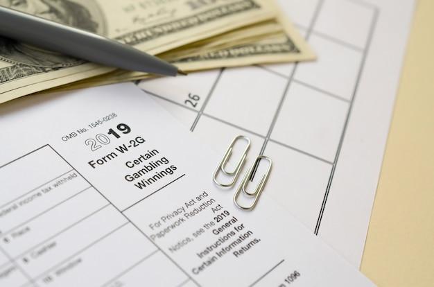 Formulário irs w-2g certas apostas em branco estão em branco com caneta e muitas notas de cem dólares na página do calendário