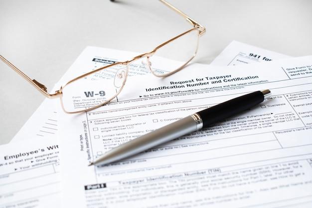 Formulário w9 das leis de imposto de renda federal. caneta e óculos