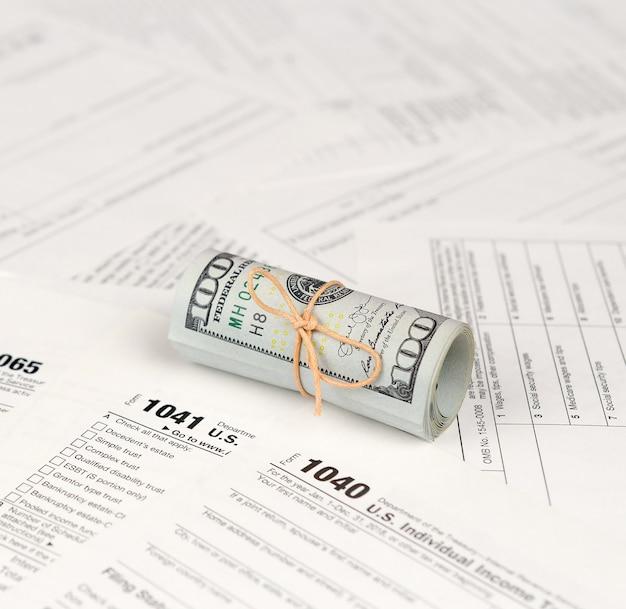 Formulários de imposto encontra-se perto de rolo de notas de cem dólares. restituição do imposto de renda