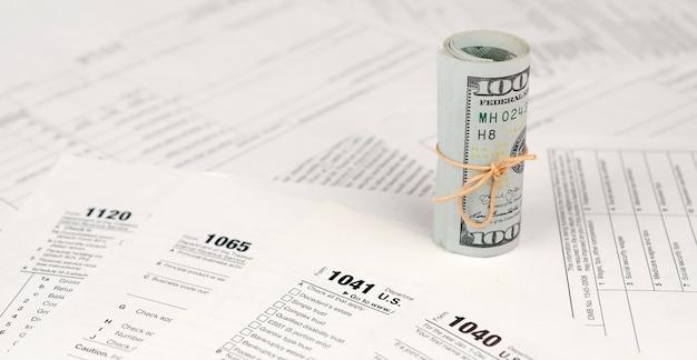 Formulários de imposto encontra-se perto do rolo de notas de cem dólares