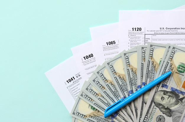 Formulários de imposto fica perto de notas de cem dólares e caneta azul em um azul claro