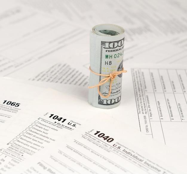 Formulários de impostos estão perto do rolo de notas de cem dólares. restituição do imposto de renda