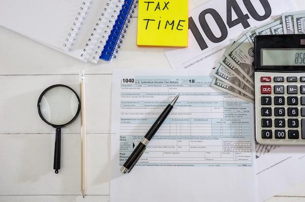 Formulários fiscais 1.040 dólares e uma caneta vista de cima
