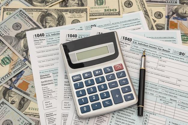 Formulários fiscais 1040 com dólares e calculadora para preencher em abril. conceito de impostos.