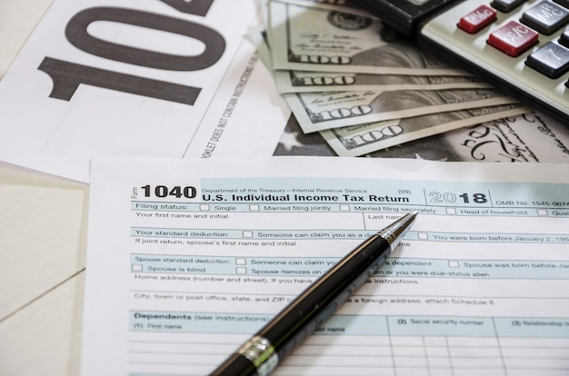 Formulários fiscais 1040 com dólares e caneta