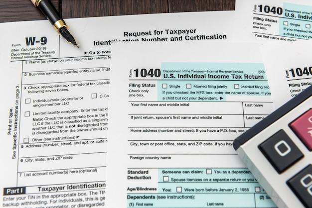 Formulários fiscais com calculadora e caneta