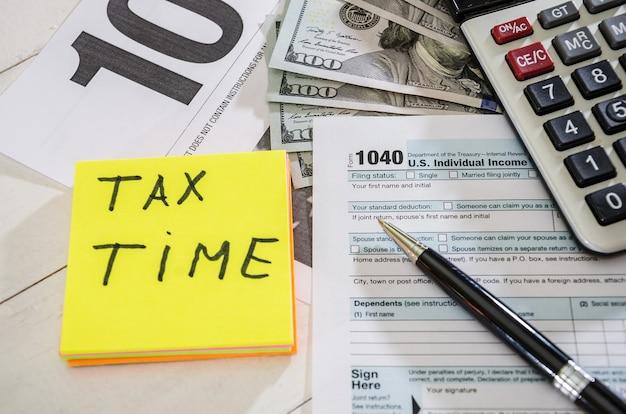 Formulários fiscais com caneta de dólares e calculadora