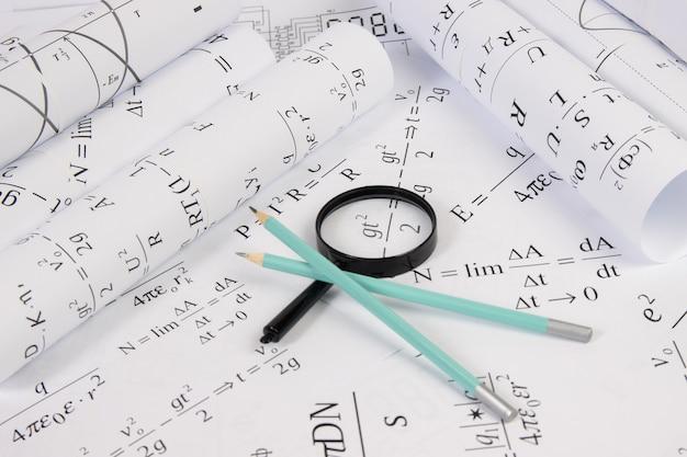 Fórmulas elétricas matemáticas de papel, lupa e lápis