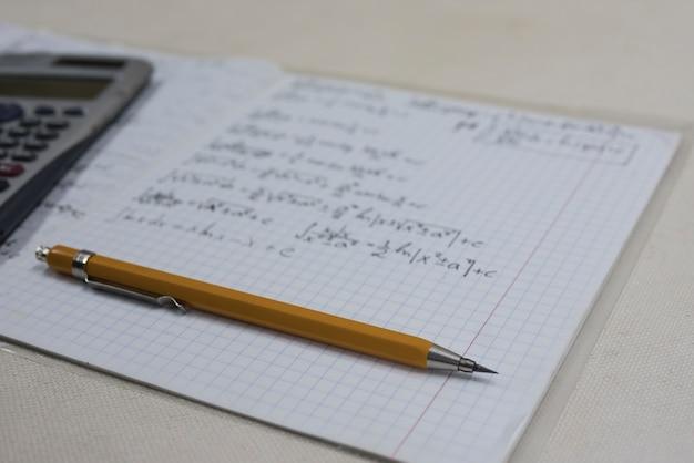 Fórmulas matemáticas no caderno, lápis e calculadora