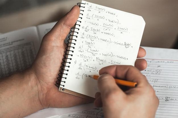 Fórmulas matemáticas são escritas a lápis em um caderno segurando um homem