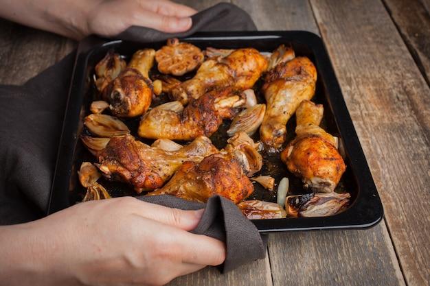 Forno assado pernas de frango com cebola.