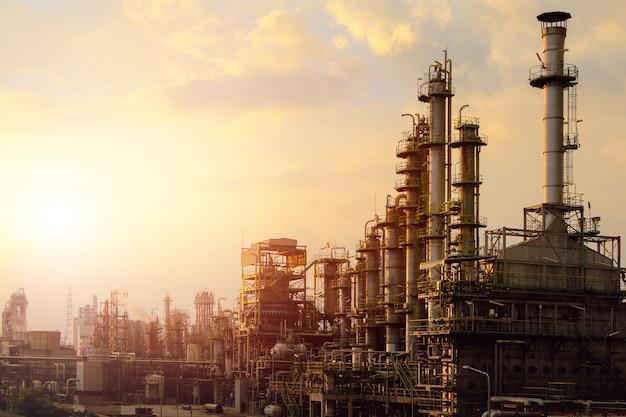 Forno industrial rachado hidrocarboneto em negócios petroquímicos no fundo do céu por do sol, fabricação de planta industrial de petróleo
