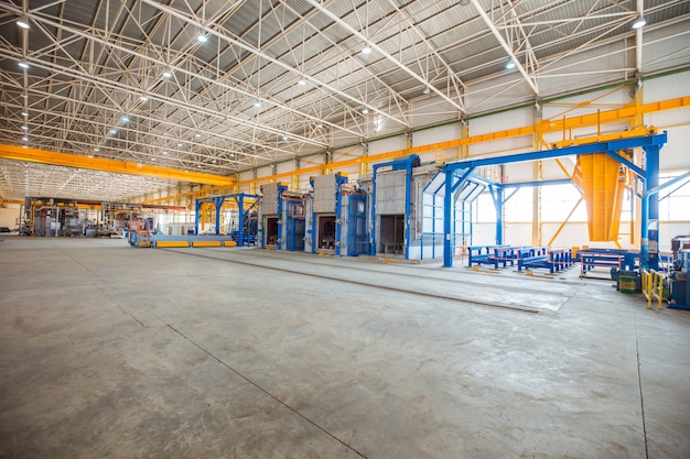 Fornos metálicos dentro de uma grande fábrica com equipamentos pesados.