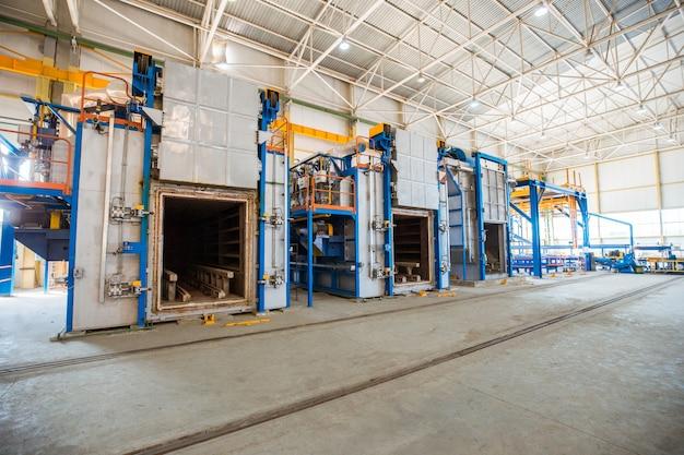 Fornos metálicos dentro de uma grande fábrica.