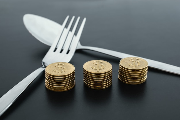 Forquilha e dinheiro no conceito escuro do dinheiro da economia do negócio da placa.