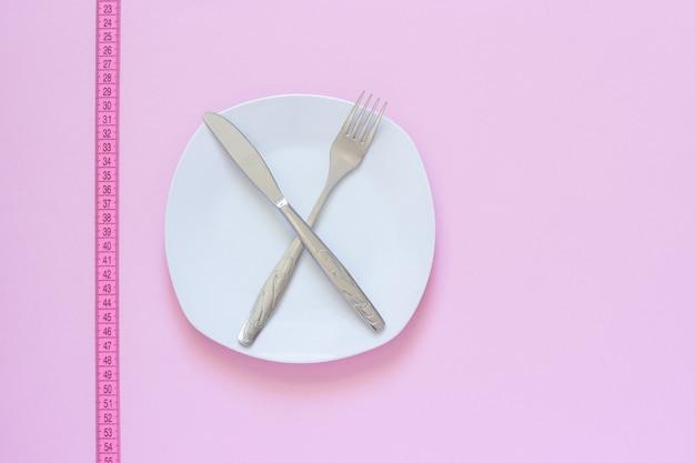 Forquilha e faca cruzadas na placa branca e fita métrica no fundo cor-de-rosa.