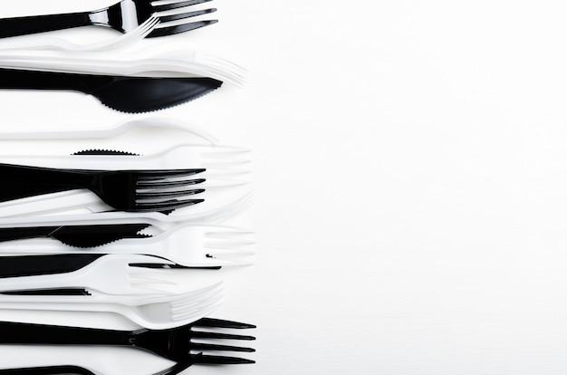 Forquilhas e facas descartáveis brancas e pretas plásticas em um fundo branco.