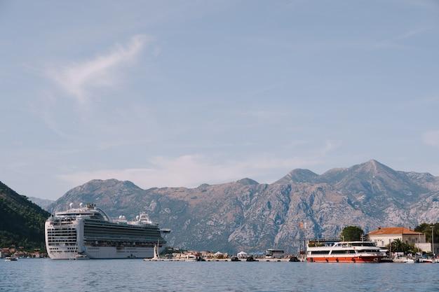 Forro no golfo de kotor em montenegro, com montanhas e céu azul com nuvens como pano de fundo