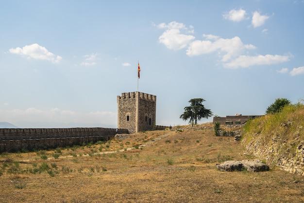 Fortaleza de skopje cercada por grama e árvores sob a luz do sol na macedônia do norte