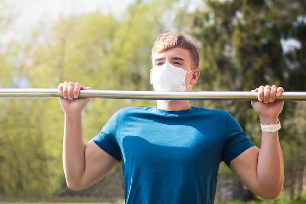 Forte ajuste cara, jovem atlético na máscara protetora médica fazendo esporte exersice, pull-up na barra horizontal, treino ao ar livre durante a quarentena. estilo de vida saudável, coronavírus, conceito de covid-19