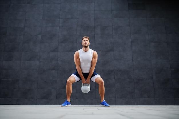 Forte caucasiano homem musculoso bonito de bermuda e camiseta em pé ao ar livre e balançando sino de chaleira. no fundo é parede cinza.