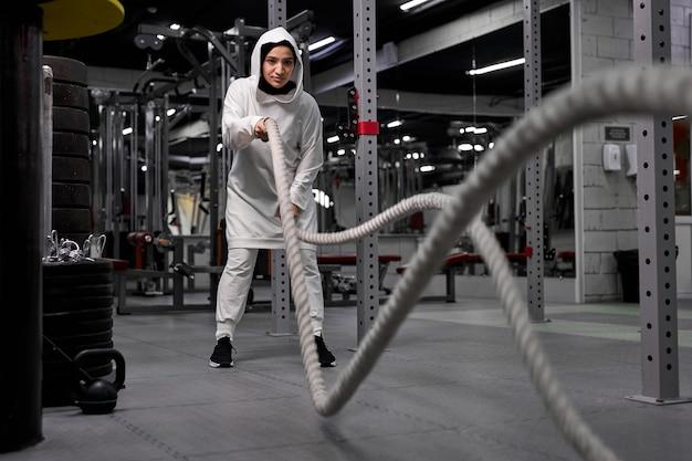 Forte desportista árabe malhando no ginásio de treinamento funcional, fazendo exercícios de crossfit com cordas de batalha, usando hijab esportivo. motivação de treino cross-fit