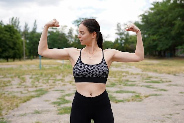 Forte e energia. bela morena jovem mostrando bíceps no braço