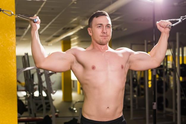 Forte fisiculturista musculoso fazendo exercícios em barras no ginásio. parte do corpo de fitness. esportes e condicionamento físico. homem de aptidão no ginásio. treino de fitness